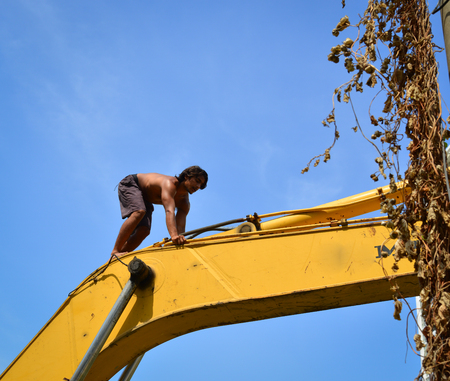 An Indian young man climbing on the construction machine at sunny day