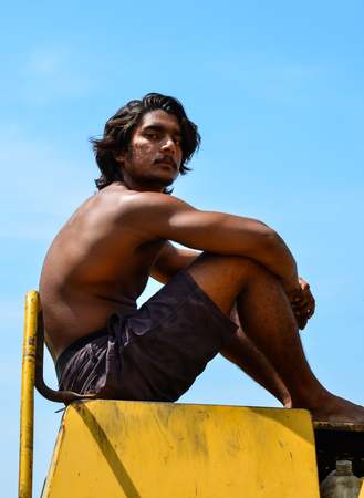 An Indian young man sitting on construction machine at sunny day in summer Stock Photo