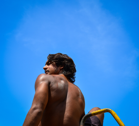 An Indian young man sitting and looking at the blue sky at sunny day Stock Photo