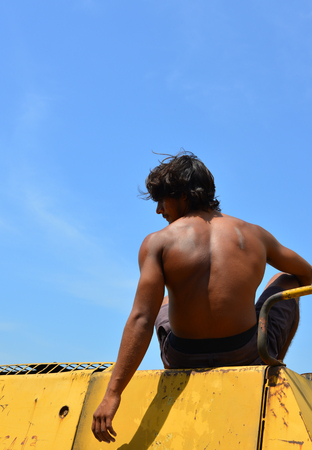 An Indian young man sitting on construction machine at sunny day Stock Photo