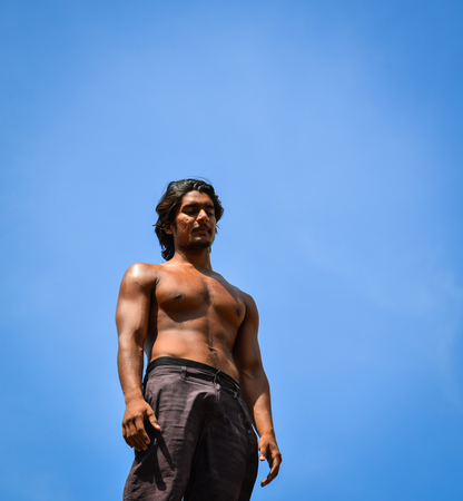 Portrait of muscle young man under blue sky in summer. Close up.