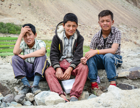 Leh, India - Jul 18, 2015. Tibetan boys sitting on road in Nubra Valley, India. 65% of children attend school, but absenteeism of both students and teachers remains high.