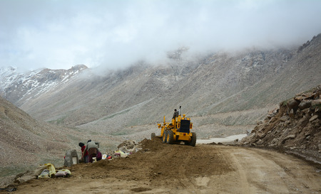 Ladakh, India - Jul 18, 2015. A road-roller working on mountain road in Leh, Ladakh, India. Ladakh is the highest plateau in the state of Jammu & Kashmir with much of it being over 3,000m.