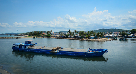 kilometres: Phu Quoc, Vietnam - May 11, 2016. A cargo boat coming to the pier in Phu Quoc, southern Vietnam. Phu Quoc is the largest island in Vietnam, with total area of 574 square kilometres.