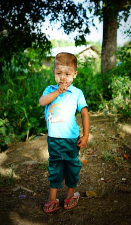 MANDALAY, MYANMAR - OCT 17, 2015. A Burmese boy posing for camera near one of holy temples of Mandalay city in Myanmar (Burma). Editorial