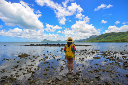 A woman standing on the beach at sunny day in Le Morne, Mauritius. Stock Photo