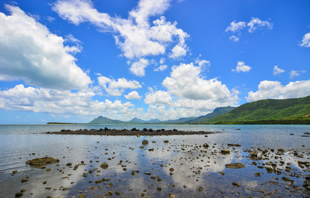 Seascape in Le Morne, Mauritius. Rocks on the beach under blue sky.