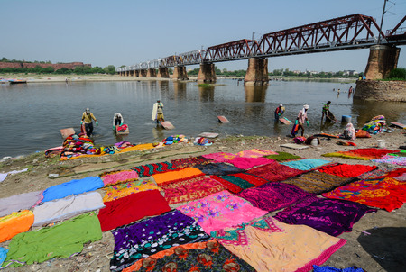 Agra, India - Jul 13, 2015. People washing and drying colorful sarees (Indian traditional dress) on the river bank in Agra, India. Agra is the city of the Taj Mahal, in Uttar Pradesh.