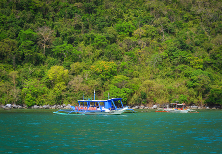 Palawan, Philippines - Apr 5, 2017. Tourist boats on the sea at sunny day in Palawan, Philippines. Palawan is one of the most beautiful islands in the world.