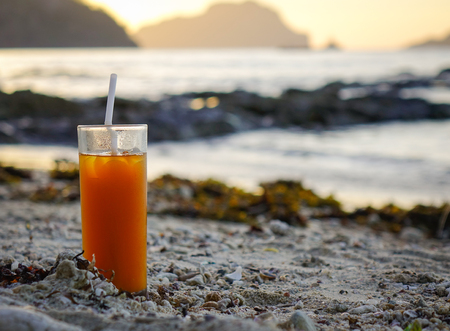 Fresh fruit juice on a wild beach at sunset in summer. Close up.