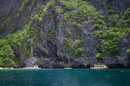 Palawan, Philippines - Apr 5, 2017. Wooden boats carry tourists on the sea at sunny day in Palawan, Philippines. Palawan is one of the most beautiful islands in the world.