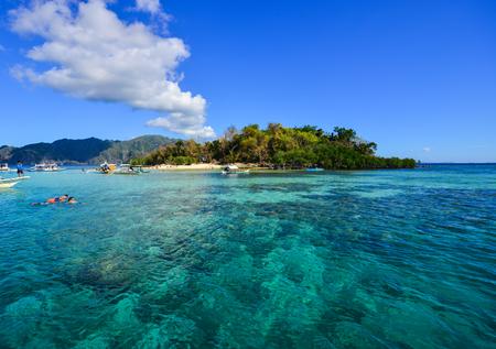 사람들은 필리핀 Coron의 화창한 날에 바다에서 수영을합니다. 코론은 필리핀 북부 팔라완에서 세 번째로 큰 섬입니다. 스톡 콘텐츠