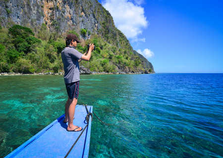 shorelines: A man standing and taking pictures on boat at sunny day in Coron, Philippines. Coron is the third-largest island in northern Palawan in the Philippines.