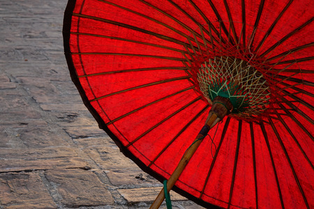 sight seeing: Red paper umbrella at ancient brick temple. Close up.