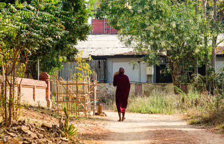 An old Buddhist monk walking on rural road at Old Town in Bagan, Myanmar. Stock Photo