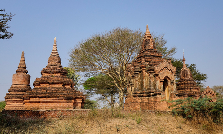 sight seeing: Buddhist temples at sunny day in Bagan, Myanmar. Bagan is home to the largest and densest concentration of Buddhist temples, pagodas and stupas. Stock Photo