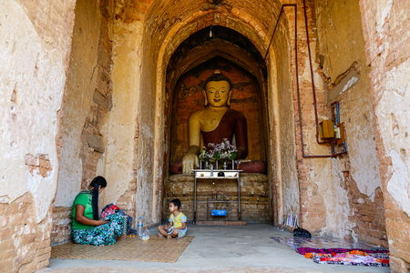 nascent: Bagan, Myanmar - Feb 17, 2016. People sitting at ancient temple in Bagan, Myanmar. The Bagan Archaeological Zone is a main attraction for the country nascent tourism industry.