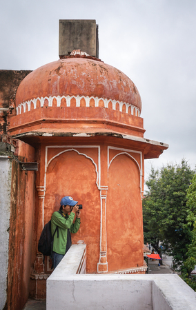 Jaipur, India - Jul 28, 2015. A tourist taking pictures at the Hawa Mahal (Wind Palace) in Jaipur, India. Hawa Mahal is one of the prominent tourist attractions in Jaipur city.
