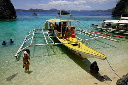 Palawan, Philippines - Apr 11, 2017. People and wooden boats on Palawan Islands in Philippines. Palawan is an archipelago of 1,780 islands on the western part of the Philippines.