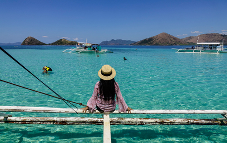 Palawan, Philippines - Apr 11, 2017. A woman sitting on wooden boat at sunny day in Palawan, Philippines. The Palawan coast is one of the most unspoilt places in the world. Editorial
