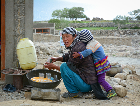 Leh, India - Jul 21, 2015. A Tibetan woman with her son at a village in Nubra Valley, India. 65% of children attend school, but absenteeism of both students and teachers remains high. Editorial