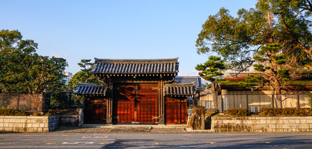 A wooden gate of the ancient palace at sunny day in Kyoto, Japan. Kyoto is famous for its numerous classical Buddhist temples, as well as gardens and imperial palaces.
