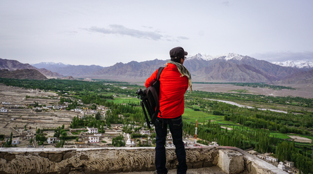 A tourist looking at mountain scenery in Ladakh, India. Ladakh is the highest plateau in the state of Jammu & Kashmir with much of it being over 3,000m.