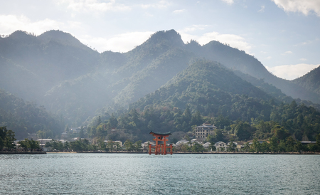 vermilion coast: Mountain scenery with floating gate (Giant Torii) of Itsukushima Shrine in Hiroshima, Japan. The temple is a UNESCO World Heritage Site.