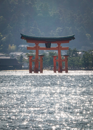 vermilion coast: View of floating gate (Giant Torii) of Itsukushima Shrine with sun light on sea in Hiroshima, Japan. The temple is a UNESCO World Heritage Site.