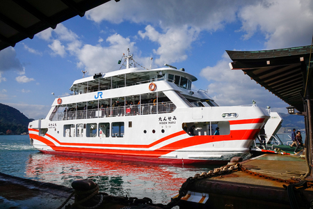 Hiroshima, Japan - Dec 28, 2015. A red ferry docking on Miyajima Island in Hiroshima, Japan. Miyajima can be reached from Hiroshima in less than an hour by train and ferry.