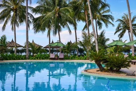 belongs: Phan Thiet, Vietnam - Mar 26, 2017. Swimming pool with palm trees in Phan Thiet, Vietnam. Phan Thiet belongs to Binh Thuan province and located 200km South of Cam Ranh Bay.
