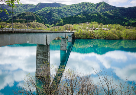 Reflection lake with the bridge and pine forest in Tohoku, Japan. The Tohoku region consists of the northeastern portion of Honshu, the largest island of Japan. Stock Photo