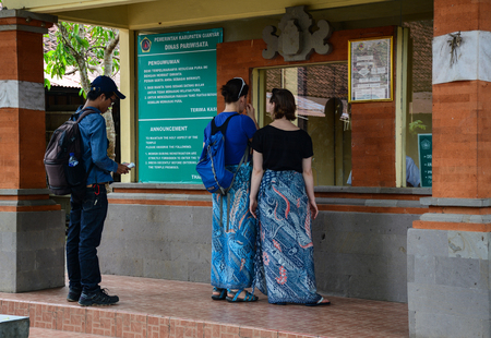 Bali, Indonesia - Apr 21, 2016. People waiting at ticket booth of Uluwatu temple in Bali, Indonesia. Bali is a popular tourist destination, which has seen a significant rise in tourists since the 1980s.