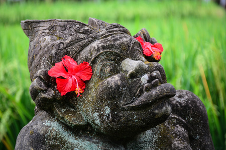 A God statue with red flowers for decorations at the ancient Hindu temple in Bali, Indonesia. Stock Photo