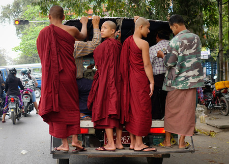 former: Mandalay, Myanmar - Feb 25, 2016. Buddhist monks standing on bus in Mandalay, Myanmar. Mandalay is the second largest city in Burma, and a former capital of Myanmar. Editorial
