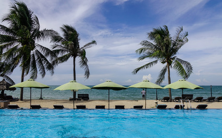 inground: Phan Thiet, Vietnam - Mar 26, 2017. Swimming pool with palm trees at sunny day in Phan Thiet, Vietnam. Phan Thiet belongs to Binh Thuan province and located 200km South of Nha Trang.