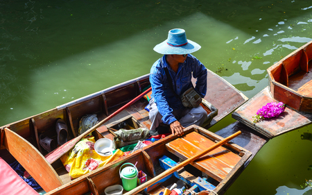 saduak: Bangkok, Thailand - Jun 19, 2017. A vendor at the Damnoen Saduak floating market in Bangkok, Thailand. This is the most famous of the floating markets in Thailand.