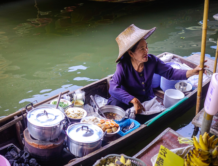 Bangkok, Thailand - Jun 19, 2017. A woman selling foods at Damnoen Saduak floating market in Bangkok, Thailand. This is the most famous of the floating markets in Thailand.