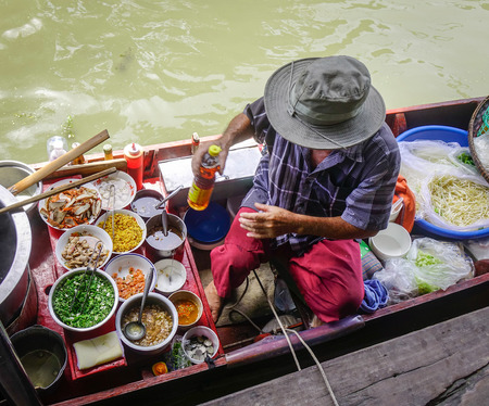 Bangkok, Thailand - Jun 19, 2017. Vendor cooking on boat at Damnoen Saduak floating market in Bangkok, Thailand. This is the most famous of the floating markets in Thailand. Editorial