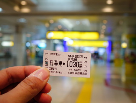 Tokyo, Japan - Dec 7, 2016. Hand holding a train ticket at the JR station in Tokyo, Japan. Railways are the most important means of passenger transportation in Japan.