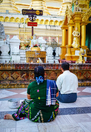 travelled: Yangon, Myanmar - Oct 16, 2015. Local people pray at Shwedagon Pagoda in Yangon, Myanmar. Shwedagon is the most famous pagoda in the world and a must see place in Yangon. Editorial