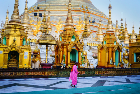 Yangon, Myanmar - Oct 16, 2015. A nun walking at Shwedagon Pagoda in Yangon, Myanmar. Shwedagon is the most famous pagoda in the world and a must see place in Yangon. Editorial