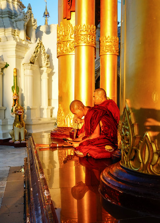 Yangon, Myanmar - Oct 16, 2015. Monks sit at Shwedagon Pagoda in Yangon, Myanmar. Shwedagon is the most famous pagoda in the world and a must see place in Yangon. Editorial