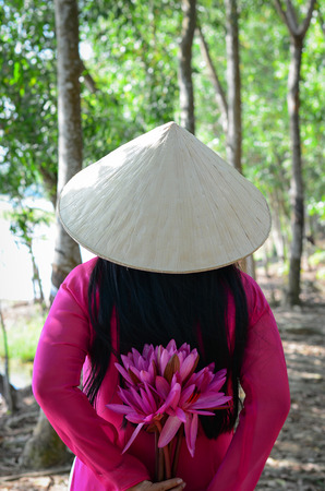 An Asian woman in traditional dress and conical hat with waterlily flowers in Southern Vietnam.