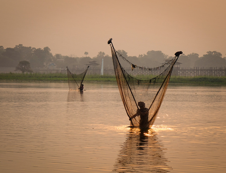 Fishermen working on lake at sunrise in Mandalay, Myanmar. Mandalay is the second-largest city and the last royal capital of Myanmar. Stock Photo