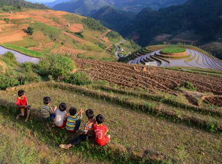 Sapa, Vietnam - May 28, 2016. Children sitting on terraced rice field in Sapa, Vietnam. Sapa is a beautiful, mountainous town in northern Vietnam along the border with China. Editorial