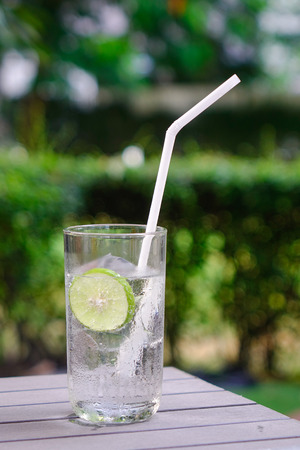 Glass of lime juice with white straw on wooden table at the summer garden. Close up.