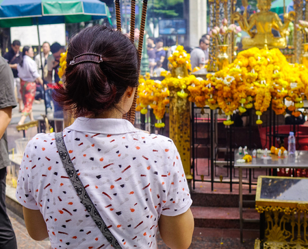 phrom: Bangkok, Thailand - Jun 20, 2017. A woman praying at Erawan Temple in Bangkok, Thailand. Thailand is Asia primary travel destination and offers a host of places to visit. Editorial