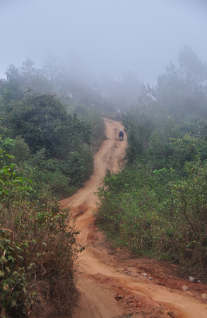 Mountain road at misty day in Dalat Highlands in Vietnam. Da Lat in Central Highlands, is centered around a lake and golf course, and surrounded by hills, pine forests. Stock fotó