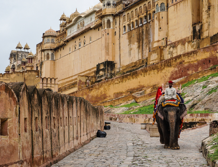 Jaipur, India - Jul 28, 2015. People riding elephant on the cobblestone path to Amber Fort in Jaipur, India. Elephant rides are popular tourist attraction in Amber Fort.
